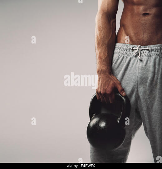 Close up image of young man's hand holding kettlebell. Crossfit workout concept with copyspace on grey background. - Stock-Bilder