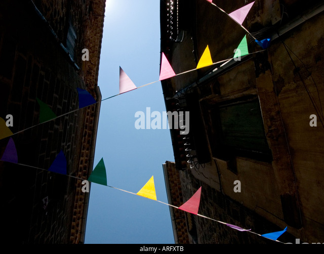 A view looking up through some colourful bunting  and roofs to a blue sky in downtown agde, france - Stock Image