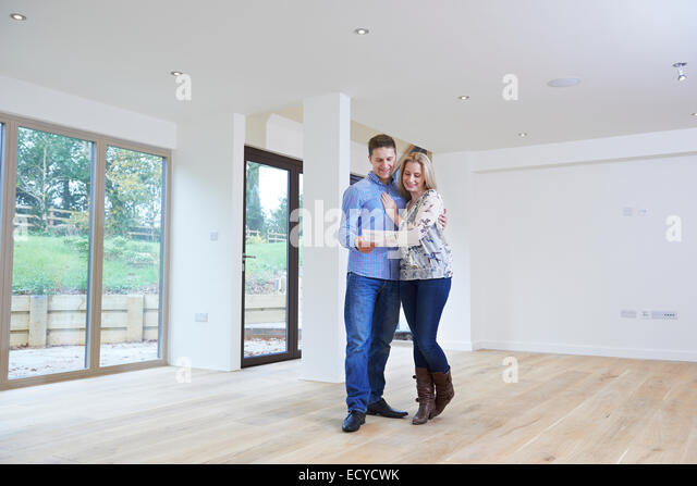 Happy Young Couple Looking At Details Of New Home - Stock Image