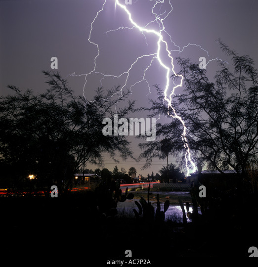 Lightning strike from front yard of home looking down neighborhood street in Tucson, Arizona, USA. - Stock Image