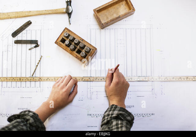 Hands of young craftswoman measuring blueprint in pipe organ workshop - Stock Image