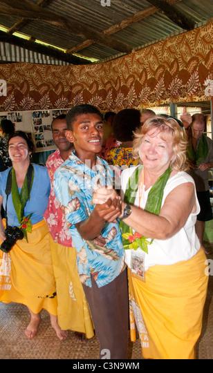 Tourists dancing with local fijians in native kava cermony  Naveyago Village, Sgatoka Valley, Sigatoka River, Viti - Stock Image