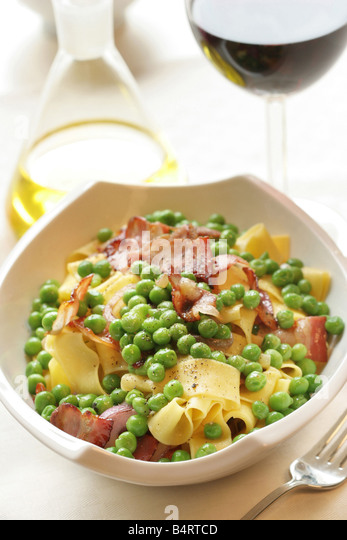 Pappardelle pasta with peas and bacon Italy - Stock Image