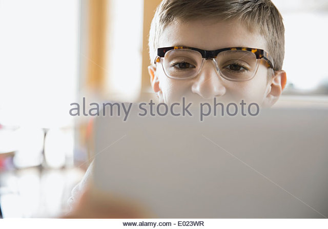 Close up of school boy using laptop in classroom - Stock Image