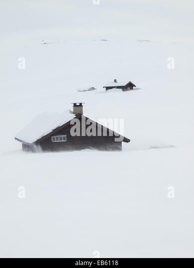 mountain huts in winter mountain landscape with wind blown snow in foreground - Stock Image