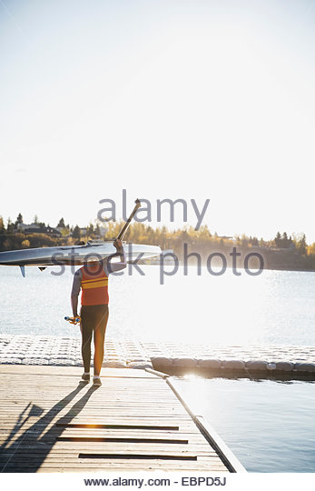 Rower carrying scull on dock at waterfront - Stock Image