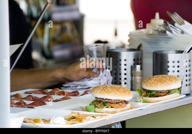 Hamburgers freshly prepared by cook waiting to be served to customers - Stock-Bilder