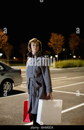 Woman alone in parking lot - Stock Image