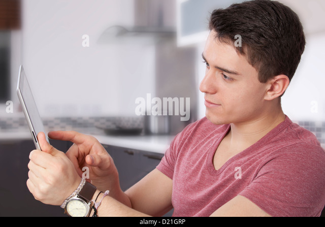 Young man using a digital tablet, looking at the screen or monitor. Situated in a modern kitchen. - Stock Image