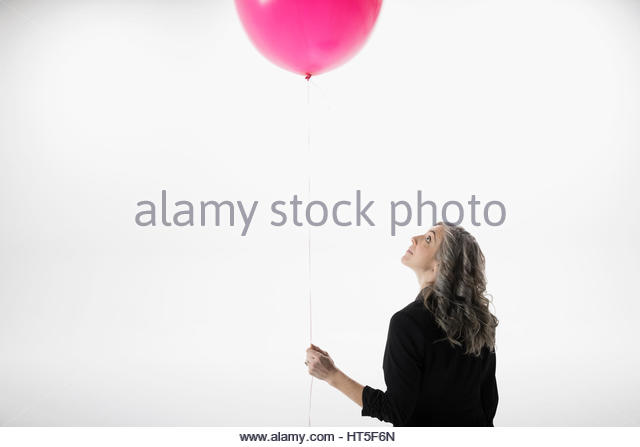 Woman holding and looking up at pink balloon against white background - Stock-Bilder
