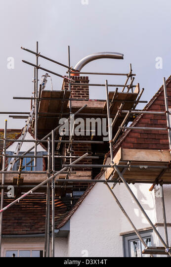 Scaffold on a house showing the flue lining coming out of the chimney pot - Stock Image