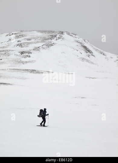 man  with heavy pack  snowshoeing through a winter mountain landscape with mountain top behind - Stock Image