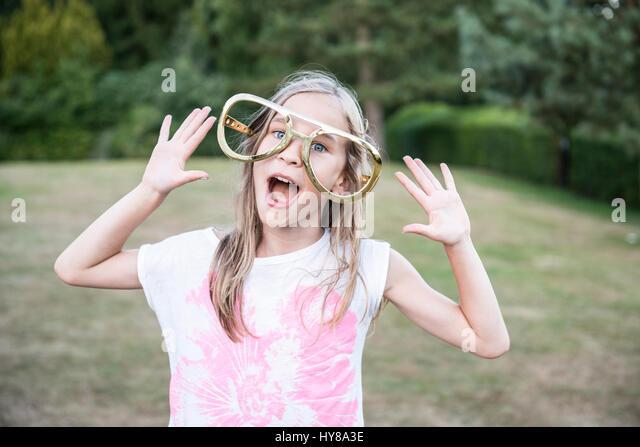 A young girl wearing oversized joke glasses - Stock Image