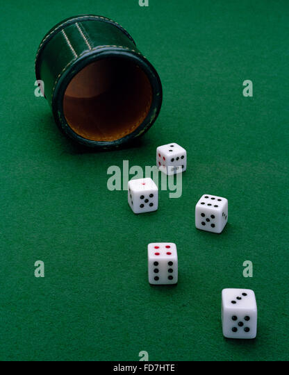 Five dice on green baize thrown from a green leather cup - Stock Image