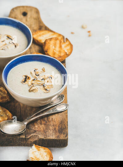 Healthy dinner with creamy mushroom soup and toasted bread - Stock Image