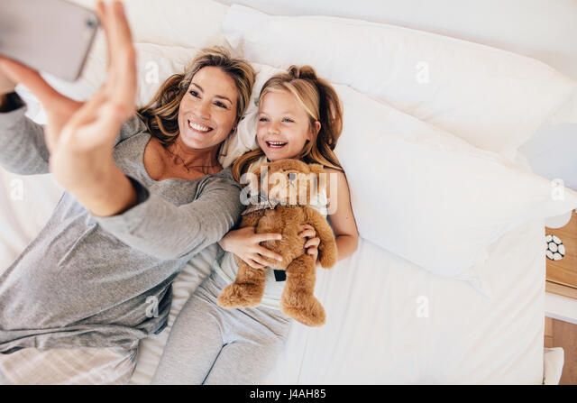 Top view shot of happy young family taking selfie with smartphone in the bed. Mother and daughter lying on bed taking - Stock Image