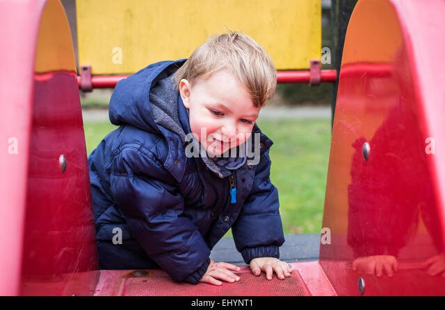 Baby boy climbing on a slide - Stock Image