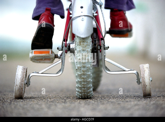 Young child on a bicycle with stabilizers or stabilisers or training wheels - Stock Image