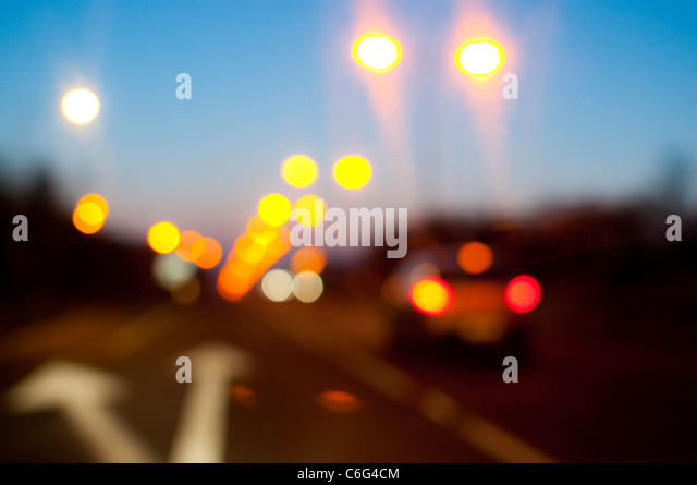 Street lights and car tail lights on a road at dusk - Stock Image