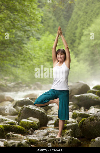 Asian woman performing Vrksasana pose yoga by the river, Lynn Valley, British Columbia, Canada - Stock Image