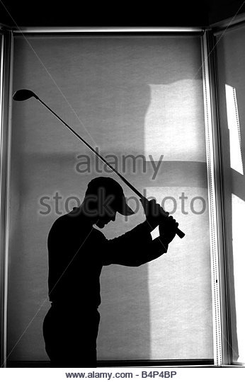 Silhouetted man practising his golf swing indoors - Stock Image