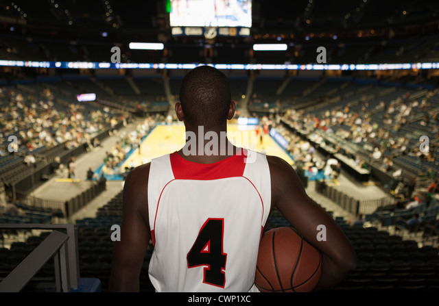 Basketball player looking down at stadium, rear view - Stock Image