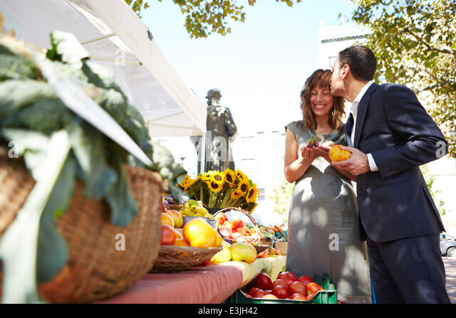 Man Kissing Woman's Forehead at Farmers Market - Stock Image
