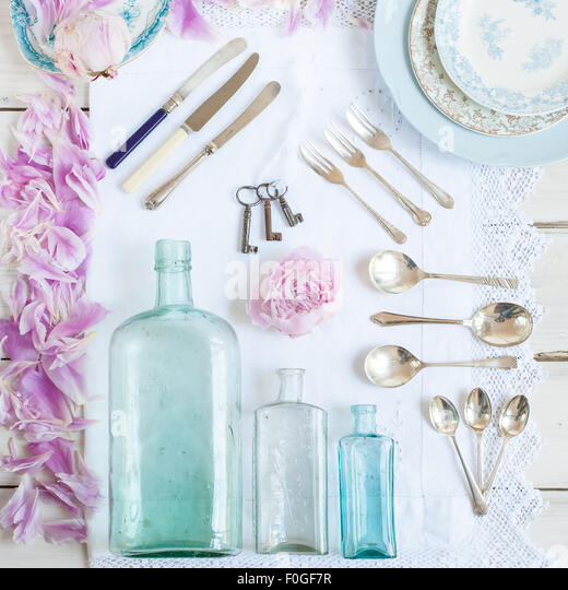 a collection of vintage bottles,  cutlery, plates, old keys, and peonies - Stock-Bilder