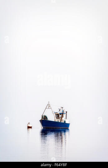 a fishing boat on a misty sea - Stock Image