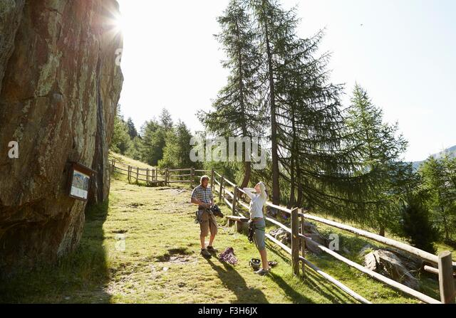 Young rock climbing couple preparing to climb rock formation, Val Senales, South Tyrol, Italy - Stock Image