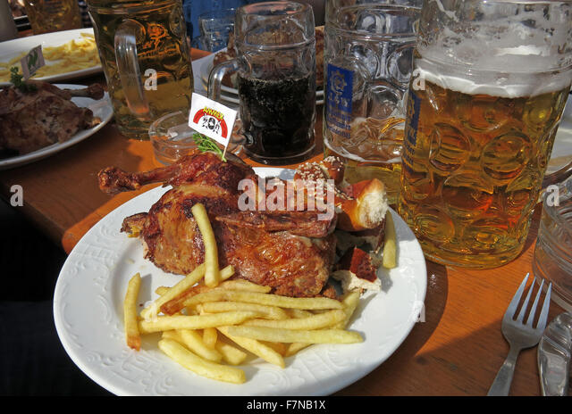 Oktoberfest beer steins and festival food, half chicken & fries, Munich, Germany - Stock Image