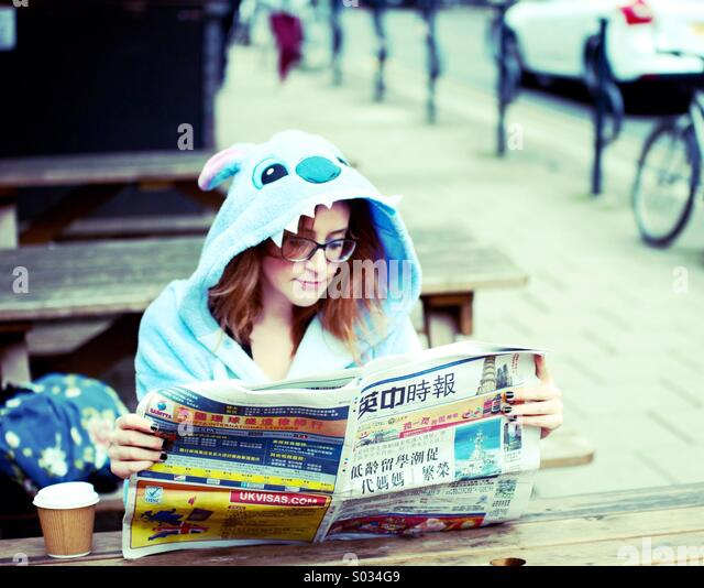 Woman in Stitch costume reading a Chinese newspaper - Stock-Bilder
