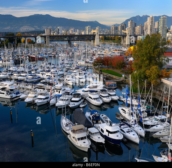 Boats moored at Granville Island Boat Yard and Burrard Marina with bridge and Coastal mountains Vancouver Canada - Stock Image