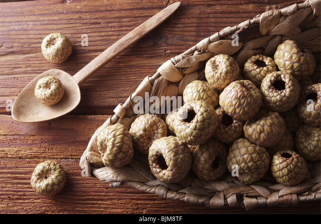 Salak or Snake Fruit (Salacca zalacca) in a wicker basket on a rustic wooden background - Stock Image