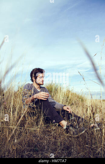 Young man alone in the fields at autumn - Stock Image