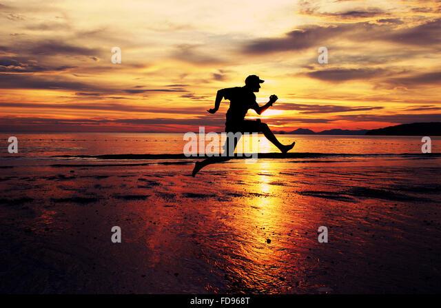 Man Running On Beach - Stock Image