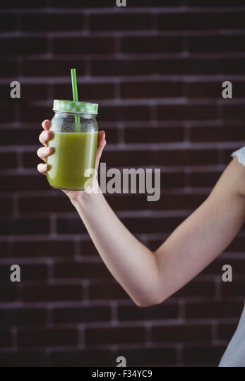 Pretty woman sipping on green juice - Stock-Bilder