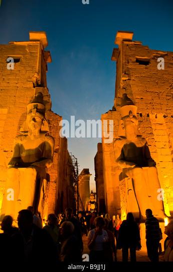 Luxor Temple Egypt entrance twilight crowd of tourists beside illuminated columns - Stock Image