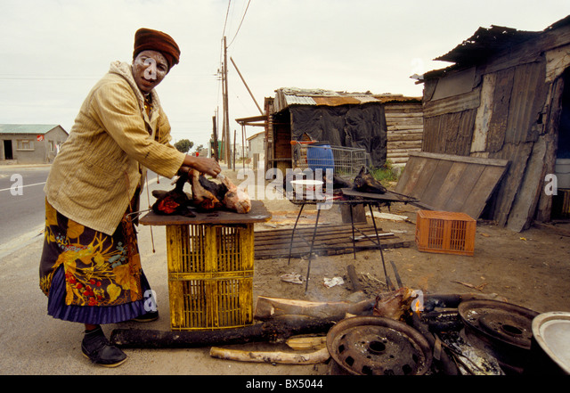 Woman prepares sheep heads to cook and sell by the roadside in a Township in Cape Town South Africa. - Stock-Bilder