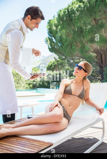 Waiter serving woman on lounge chair at poolside - Stock Image