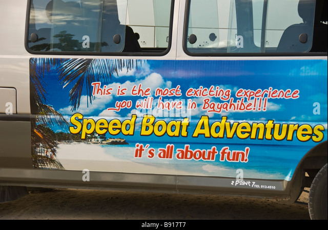 Speed boat adventures sign painted on side of bus  Bayahibe fishing village Dominican Republic tourist destination - Stock Image