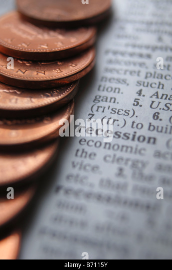 a stack of coins resting on the definition of recession in a dictionary - Stock Image