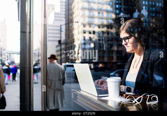 Businesswoman using laptop while sitting at coffee shop seen through window - Stock-Bilder