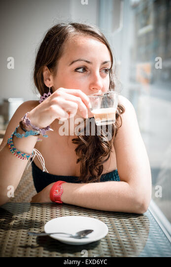 young beautiful woman drinking coffee at the coffee bar - Stock Image