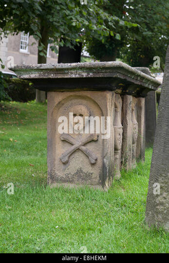 Church graveyard at Eyam Derbyshire Peak District England United Kingdom showing plague headstone with skull and - Stock Image
