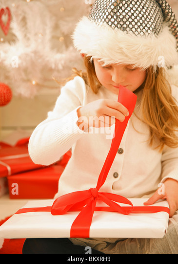 Close up of a girl in a furry hat unwrapping a Christmas gift - Stock Image
