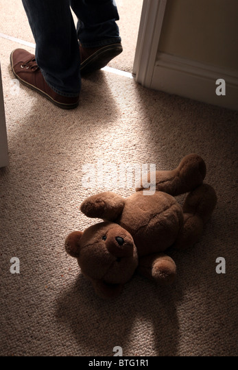 Child's teddy bear lying on the floor of a carpeted room as a man's feet step in through an open door - Stock Image