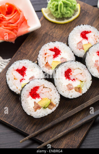 Futomaki with tobiko and shrimps on a wooden board - Stock Image