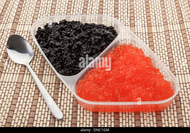 Close up of red and black caviar in a plastic container - Stock Image