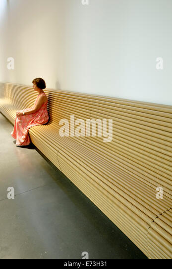 Woman sitting on bench made of cardboard tubes, Aspen Art Museum (by architect Shigeru Ban), Aspen, Colorado USA - Stock Image